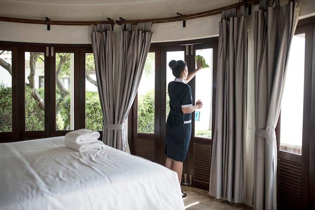 Huishoudster die een hotelvenster schoonmaakt