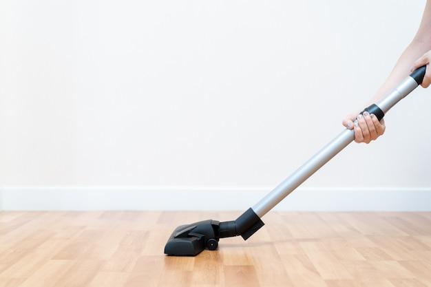 Huishoudster die vacuümmachine schone houten vloer in het huis gebruiken.