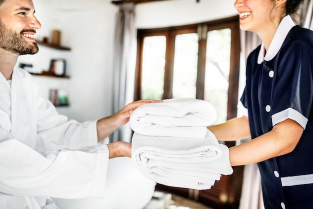 Huishoudster die verse handdoeken overhandigt