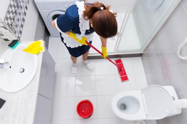 Huishoudster in een hotel die een vloer dweilt in een schone witte badkamer met een dweil, uitzicht van bovenaf