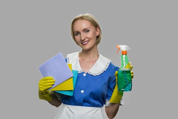 Huishoudster in uniform met schoonmaakbenodigdheden. vrij glimlachend kamermeisje met vodden en wasmiddelen. huis schoonmaak dienstverleningsconcept.