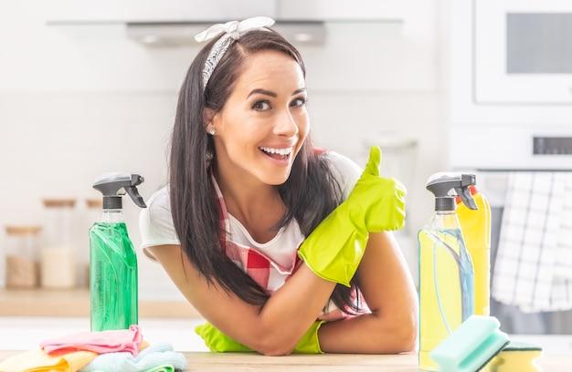 Huishoudster leunt met haar ellebogen op een bureau, met gele rubberen handschoenen duim omhoog met verschillende flessen ontsmettingsmiddel om haar heen.