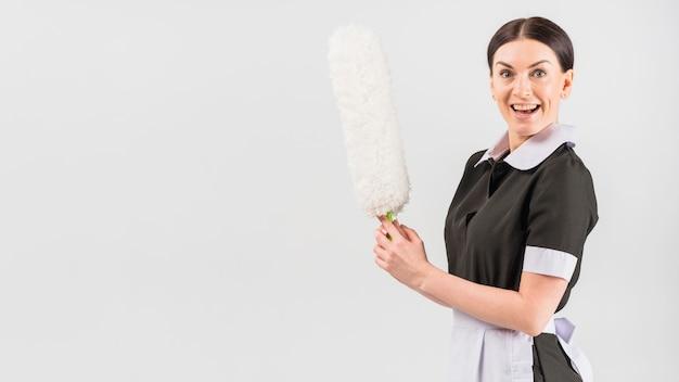 Huishoudster met blij verrast gezicht en stofdoek