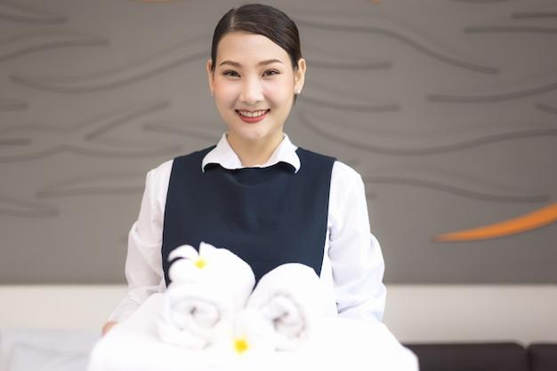 Huishoudster met handdoeken in een hotel, jong kamermeisje met schone handdoeken in de slaapkamer, perfecte roomservice