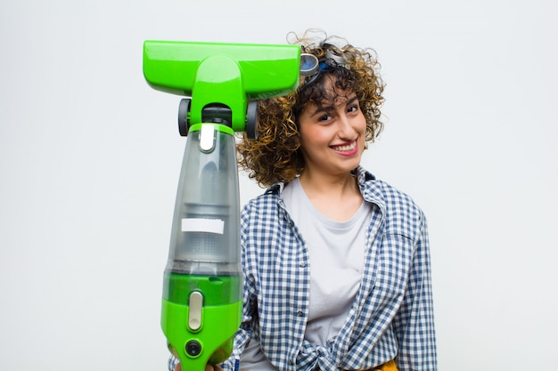Huishoudster mooie vrouw met een stofzuiger