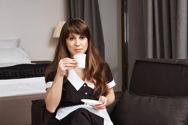 Huishoudster op haar hoede voor reinheid. binnenschot van kalm en zeker meisje in eenvormige zitting op bank en het houden van kop, het drinken van koffie met ontspannen uitdrukking, met onderbreking van het schoonmaken van appartement