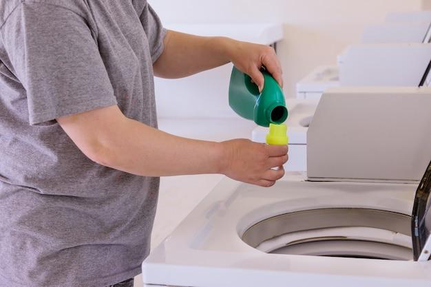 Huishoudster vrouw giet het vloeibare poeder in de wasmachine op de wasruimte