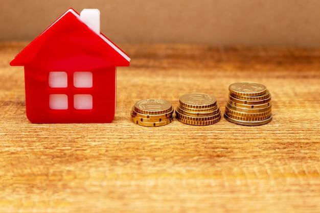 Huishuis op de inzet muntstukken achtergrond euro stapel onroerend goed concept uitgaven