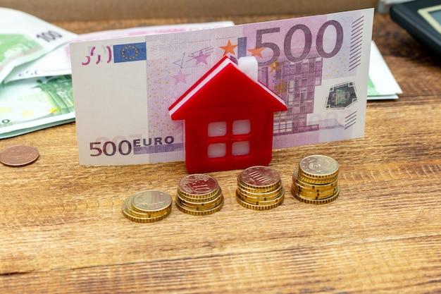 Huishuis op het ingezette onroerende goederen muntstukken achtergrond euro stapelpak