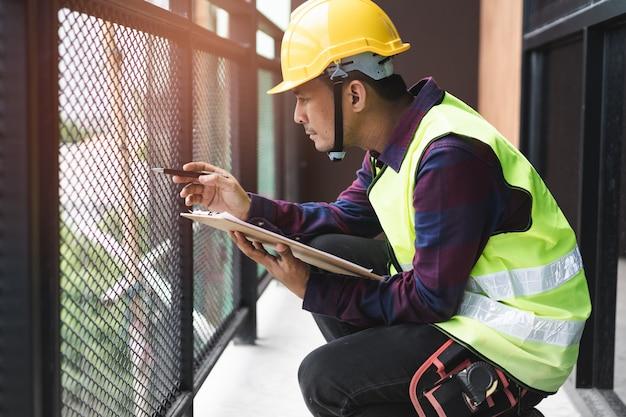 Huisinspectie consultancy. inspecteur die materiaal van balkon controleert en zoekt naar breuk.