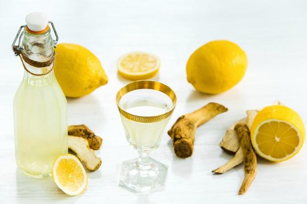 Huiskalklikeur in een glas en verse citroenen en limoenen op wit