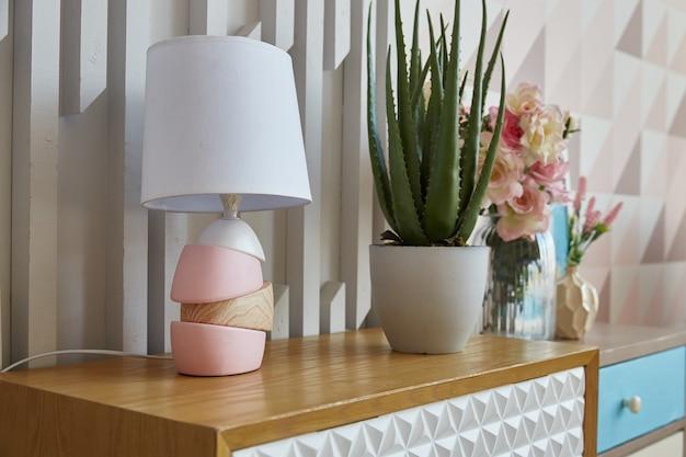 Huiskamer. lamp en bloem ingegoten op een ladekast in de kamer. interieur decoratie