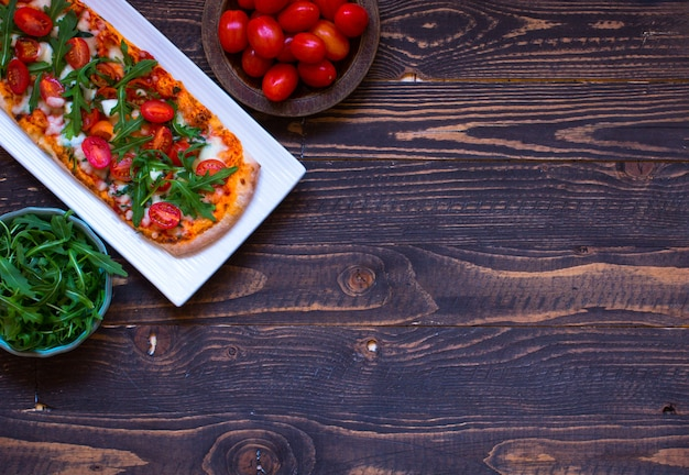 Huismeid verse pizza met tomaten, rucola en mozzarell