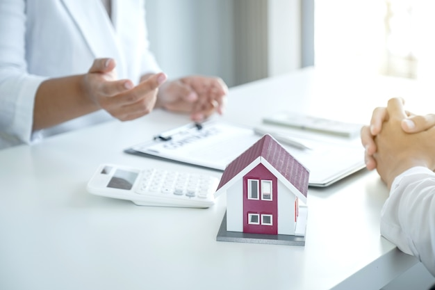 Huismodel. de makelaar legt het zakelijke contract, de huur, de aankoop, de hypotheek, een lening of woningverzekering uit aan de vrouwelijke koper.
