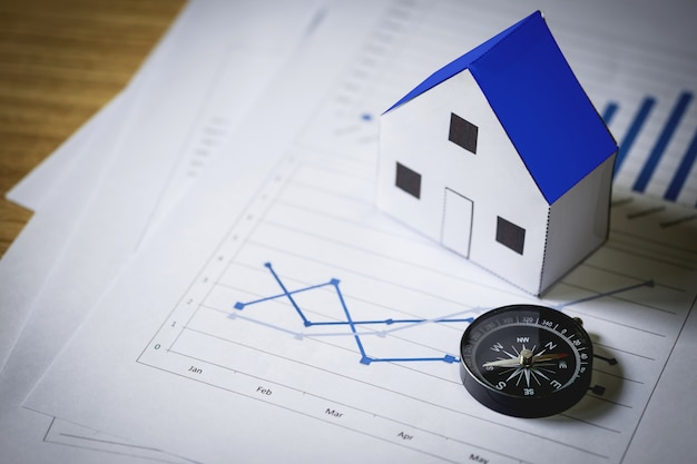 Huismodel en kompas op plan achtergrond, real estate concept