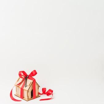 Huismodel en metaalsleutel die door rood lint wordt gebonden met ruimte voor tekst