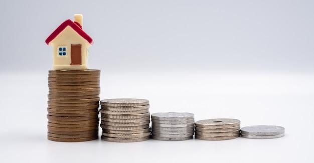 Huismodel en munt voor concepten voor financiën, sparen en bankieren