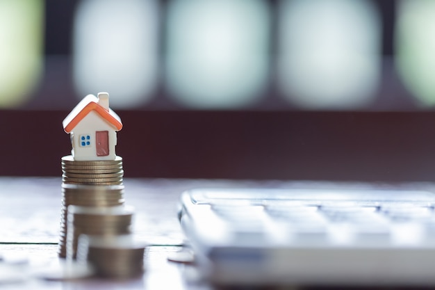 Huismodel en muntstukkenstapels met calculator als achtergrond. concept voor bezitsladder.