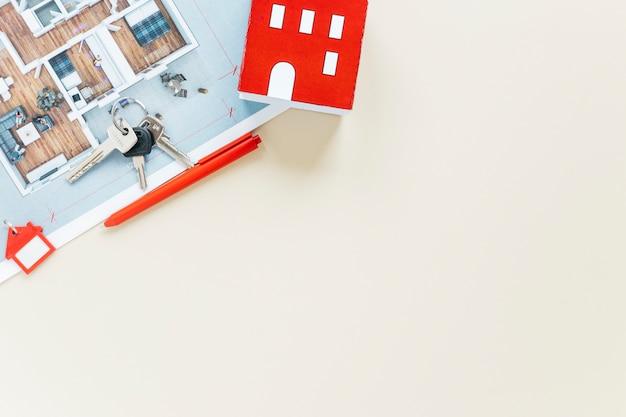 Huismodel en sleutels met blauwdruk op witte achtergrond wordt geïsoleerd die