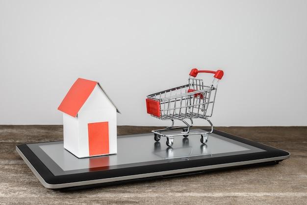 Huismodel en winkelwagen op tablet