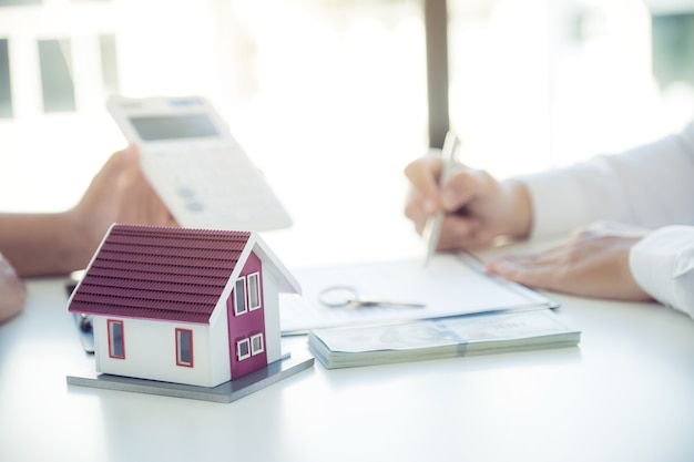 Huismodel. handtekening van het contract nadat de makelaar het zakelijke contract, de huur, de aankoop, de hypotheek, een lening of de woningverzekering aan de koper heeft uitgelegd.