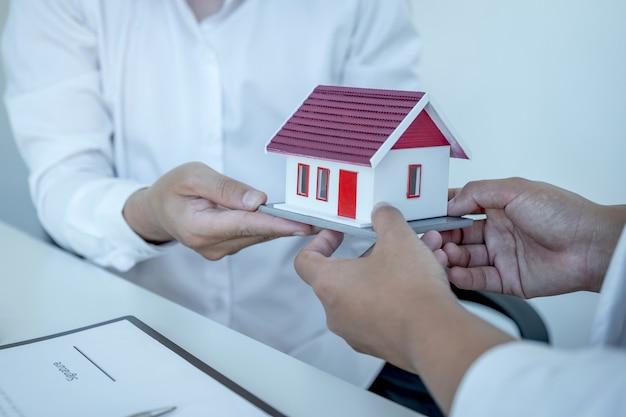 Huismodel in handen, de makelaar legt het zakelijke contract, de huur, de aankoop, de hypotheek, een lening of de woningverzekering uit aan de zakelijke koper.