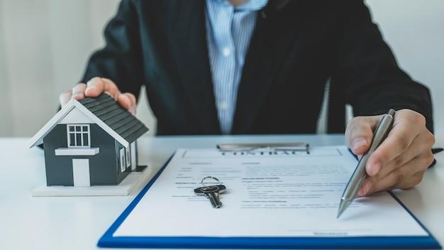 Huismodel. makelaar hand met pen en uitleg over het zakelijke contract, huur, koop, hypotheek, lening of woningverzekering.