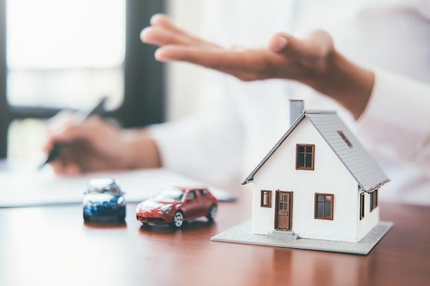 Huismodel met makelaar en klant bespreken voor contract om huis, verzekering of lening onroerend goed te kopen.