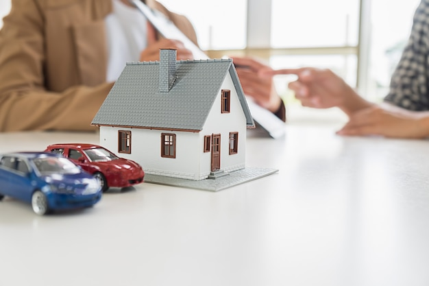 Huismodel met makelaar en klant die voor contract bespreken om huis te kopen