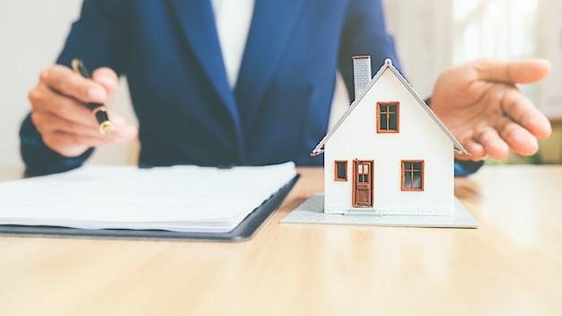 Huismodel met makelaar en klant die voor contract bespreken om huis, verzekering of leningonroerende goederenconcept te kopen