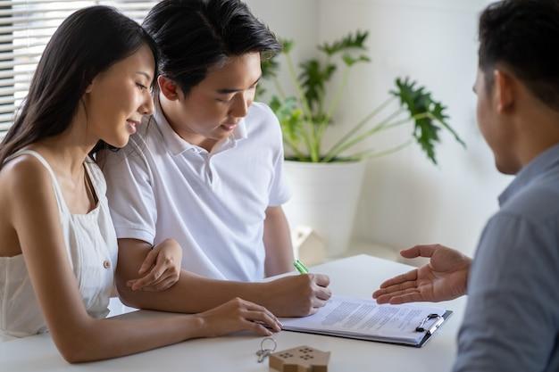 Huismodel met makelaar en klantcontract om huis te kopen