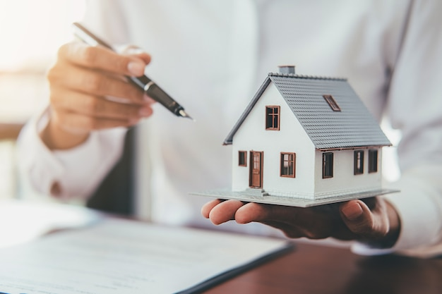Huismodel met onroerende goederenagent en klant die voor contract bespreken om huis te kopen