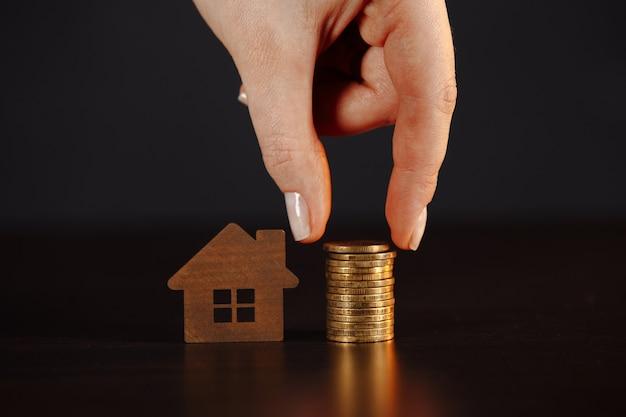 Huismodel met stapel munten. de hand van de vrouw maakt besparingsplannen voor huisvesting