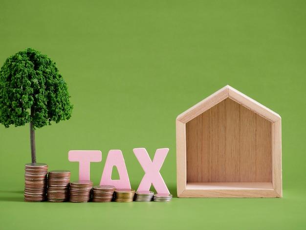Huismodel met woordbelasting en muntstukken op groene achtergrond. ruimte voor tekst