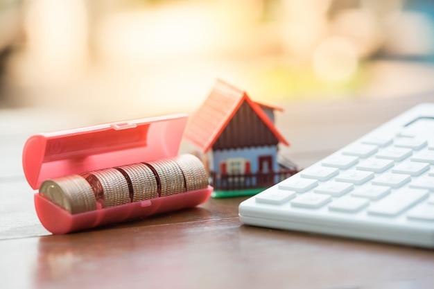 Huismodel, muntenstapel en rekenmachine. concept voor bezitsladder, hypotheek en onroerende goedereninvestering.