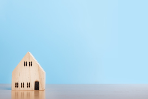 Huismodel op blauwe achtergrond. gezinswoning, verzekeringen en vastgoedbeleggingen in onroerend goed. ruimte kopiëren.