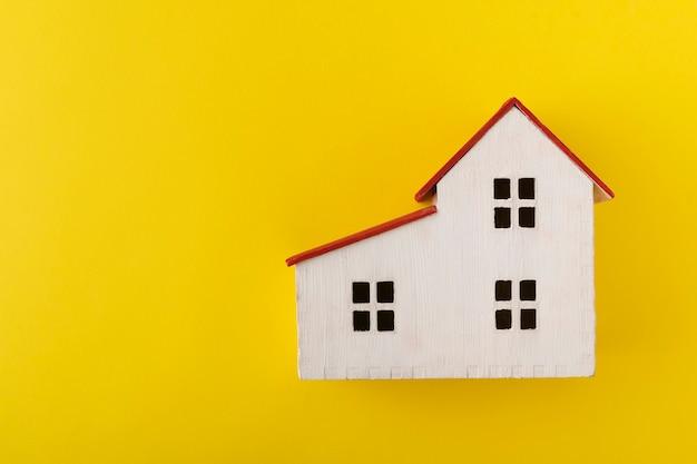 Huismodel op gele achtergrond. speelgoed huis. eigendom.