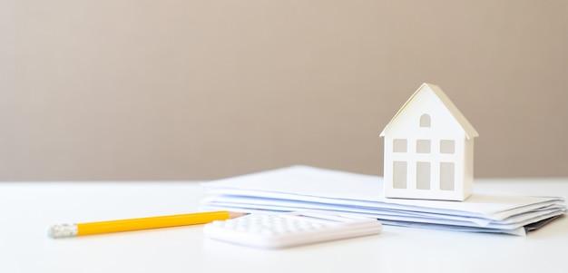 Huismodel op postbrief met calculator en potlood voor hypotheeklening en huisgebruik