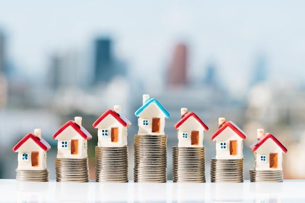 Huismodellen bovenop muntstukkenstapel met stadsachtergronden.