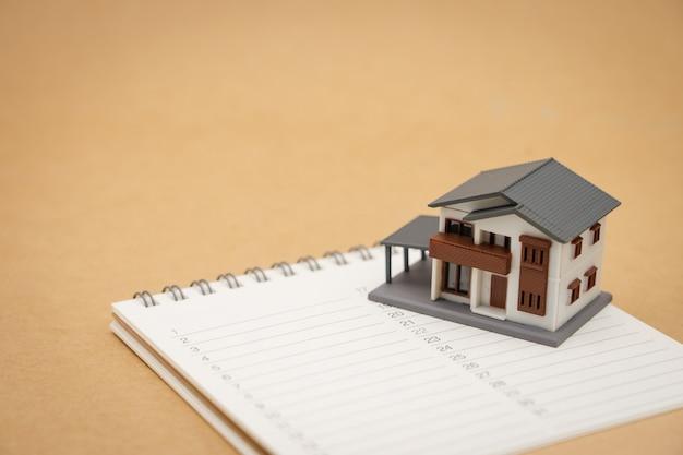 Huismodellen geplaatst op een ranglijst van boeken (lijst). home reparatie en constructie.