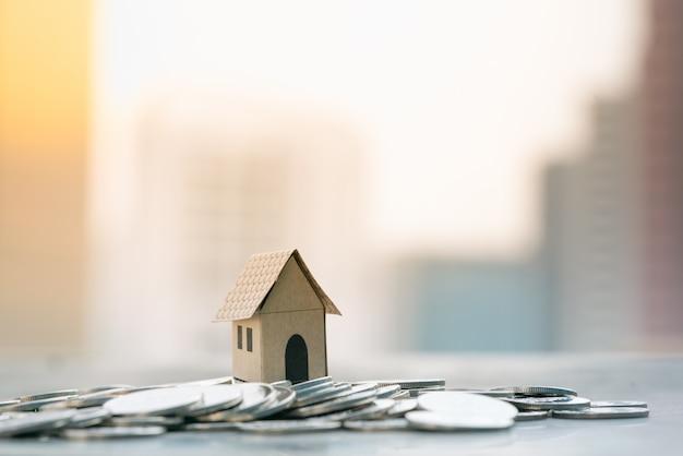 Huismodellen op stapel van munt met stadsachtergronden.