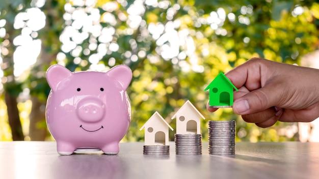Huisplannen op een stapel munten en groene huisontwerpen ideeën voor investeringen in onroerend goed