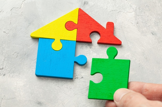 Huispuzzel woonkrediet. delen van het huis worden samengebracht. mannenhand met puzzelstukje.