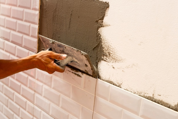 Huisrenovatie, keramische tegels aan de muur leggen