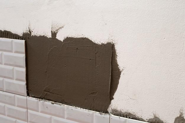 Huisrenovatie, keramische tegels op de muur leggen.