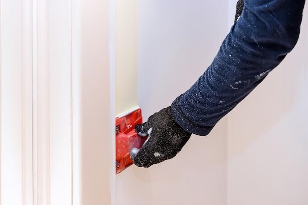 Huisrenovatie op werkende aannemersschilderhanden met het schilderen van de muur in hoekverf edger