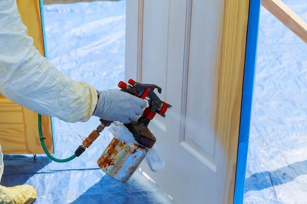 Huisreparatie verf de houten deur in witte kleur met een spray