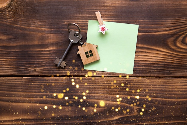 Huissleutel met sleutelhanger in de vorm van een huisje op een houten ondergrond