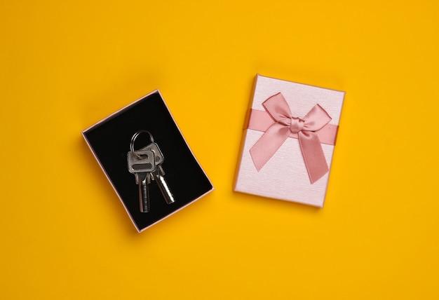 Huissleutels in een geschenkdoos met een strik op een gele achtergrond. huisvesting als cadeau. bovenaanzicht