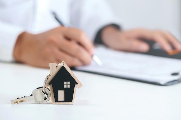 Huissleutels met sleutelhanger in de vorm van een huis aan de voorkant en man tekent contract achter huissleutels. concept voor onroerend goed, verhuizen of onroerend goed huren